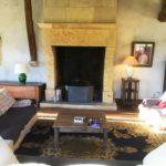 Salon avec cheminée en pierres jaunes